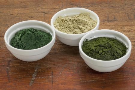 kelp, chlorella and hawaiian spirulina powders - nutritional supplements from a sea - ceramic bowls against grunge wood