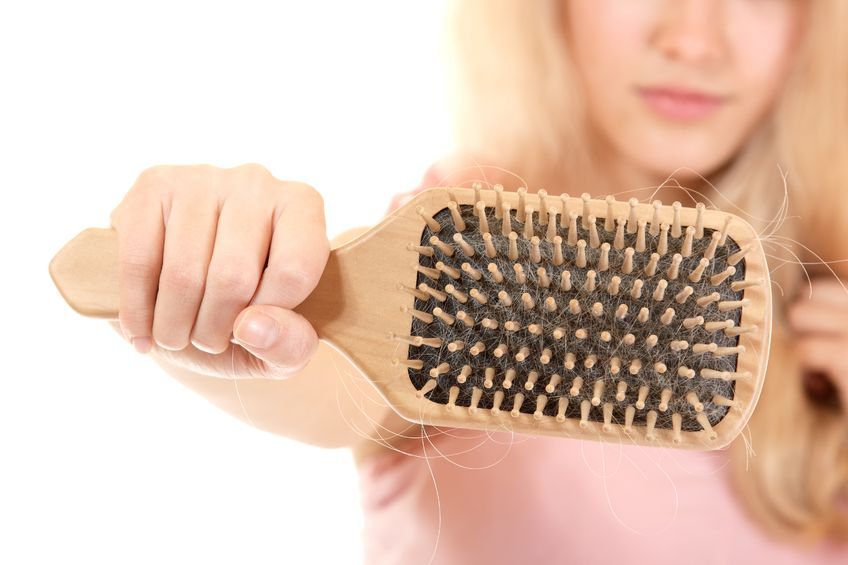 women with hair problem holding loss hair comb in hand