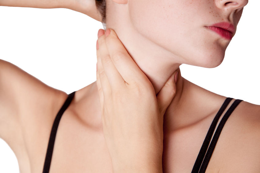 closeup view of a young woman with pain on neck or thyroid gland.