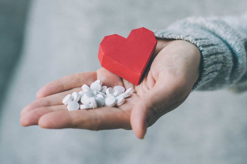 white pills and paper heart in hands. medicine and health care concept. toned image