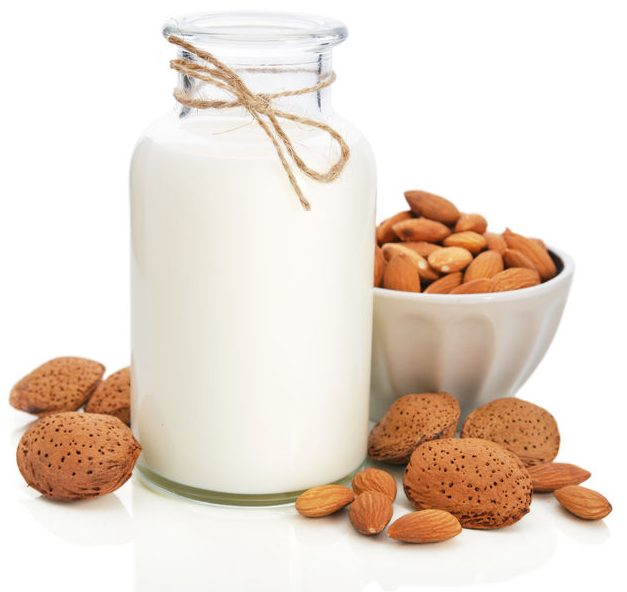 almond milk in bottle with nuts isolated on white background
